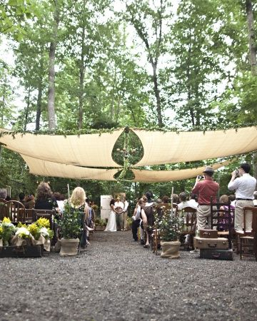 """The ceremony site featured a collection of chairs amassed by the couple over their year of searching flea markets, yard sales, and online. Katie and Jon turned chandeliers into candelabras and sun sails were strung on galvanized cables overhead, along with ivy garlands and twinkly lights. To create an """"inside-out"""" feeling, windows were hung along the perimeter."""