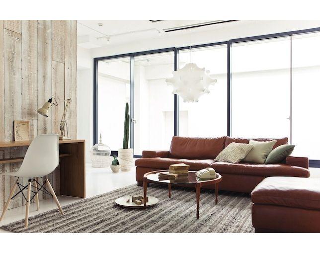 茶色の革のソファにホワイトインテリアでおしゃれなリビングスペース