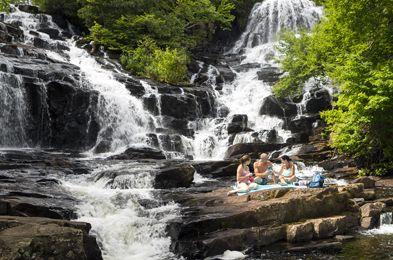 Une jeune famille en pique-nique aux des chutes Waber. (passer par l'entrée de St Jean des Piles)