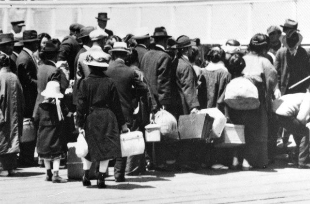 "Japanese immigrants, dockside at Bainbridge Island, Washington. ""Immigrants who cleared processing boarding a ferry to San Francisco, and a new life in America. ca. 1915."""