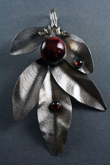 sterling silver, hand patterned leaves, with a pottery stone and garnets. $120