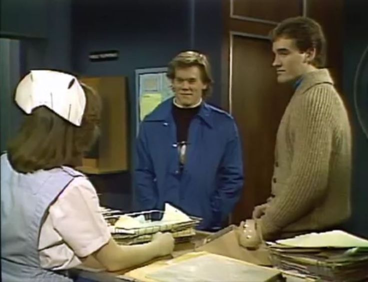 APRIL 1980--Tim Werner, now being played by KEVIN BACON, returns to Springfield. Tim's return is not a happy one. A scandal at the school he was attending led to him being expelled, which might jeopardize his athletic scholarship. He is worried about anyone finding out, especially his mother, Dr. Sara McIntyre. Here Tim is joined by Kelly Nelson (JOHN WESLEY SHIPP) and Hilary Bauer (MARSHA CLARK) at Cedars Hospital.