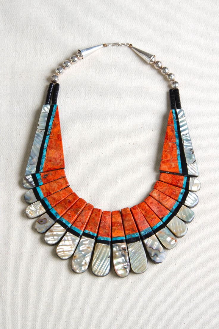 Make a statement with this wonderful Santo Domingo necklace. The Santo Domingo Pueblo is located in New Mexico.  These artists are known for their fabulous inlay and extravagant use of color. Mother of pearl, black jet, orange sponge coral and turquoise are inlaid on black jet and strung on sinew. Black jet beads and sterling silver plated beads, cones and clasp finish the necklace. This is an unforgettable piece to add to your collection.