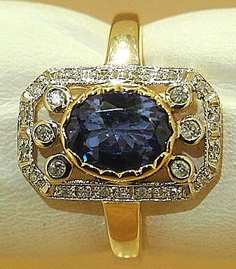 This stunning ring is from the Art Deco period, about 1918 to 1925. It features a large oval Tanzanite gem on 9 carat yellow gold and white gold settings with d