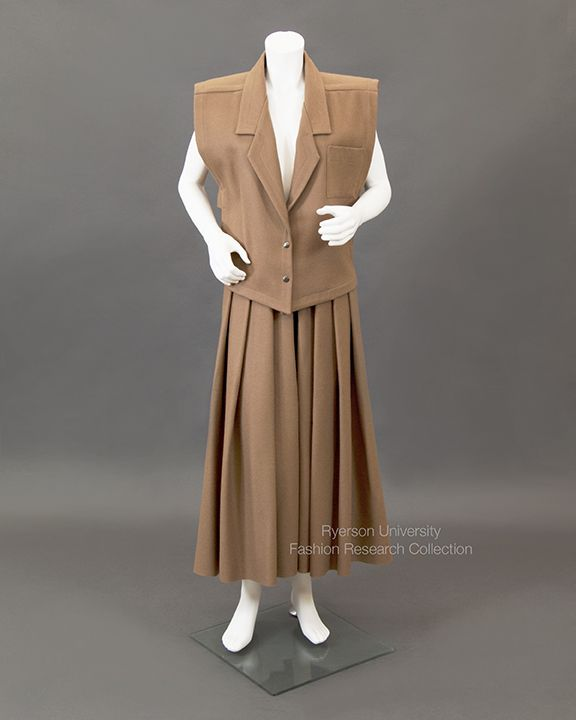 Brown wool vest with tab sides and blazer-like collar, 2 metal snap closures; matching midi-length wool skirt with paper-bag waist and unfinished hem, belt with metal snap closure detail. By Linda Lundstrom. C. 1990s.  FRC 2009.01.391