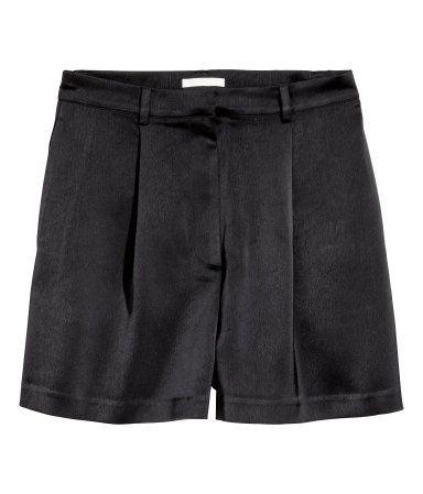 Sort. Korte shorts i forholdsvis kraftig satin. Shortsene har læg foroven. Sidelommer og paspoleret baglomme. Høj talje. Gylp med lynlås og knap.