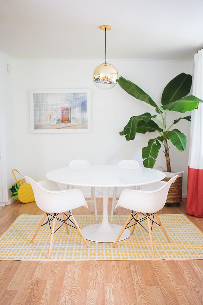 Bright, white dining room with mod furniture and a gold pendant light