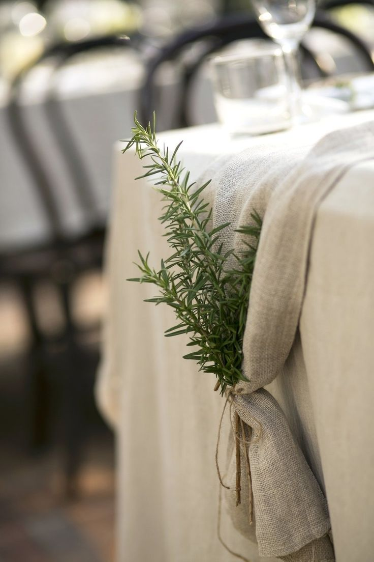 Burlap table runners with sprigs of rosemary tied at the ends