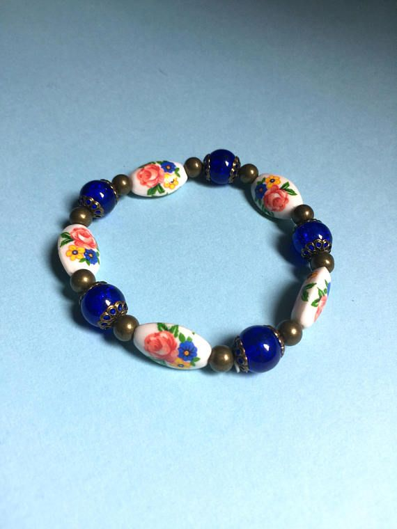 Handmade bracelet for that Vintage style loving gal in your life! A perfect gift for Mothers Day, a birthday, an anniversary, the holidays, or to show you care!  This bracelet is made with stretchy elastic string, so it fits most sizes of wrists easily with no difficult latches. In this particular bracelet, red, blue and yellow floral elongated porcelain beads compliment deep blue Crackle glass beads, tied together with antique bronze findings. Larger quantities are unavailable for this…