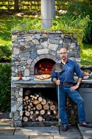Northern Westchester's Stanley Tucci in front of his home's outdoor pizza oven. He and his parents, Joan and Stan, wrote 'The Tucci Cookbook,' a collection of family recipes, with chef Gianni Scappin.