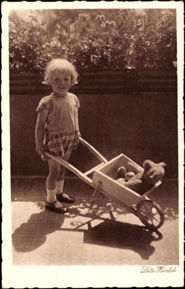 Postcard / Post Card Lotte Herrlich, Young child with teddy bears in a wheelbarrow