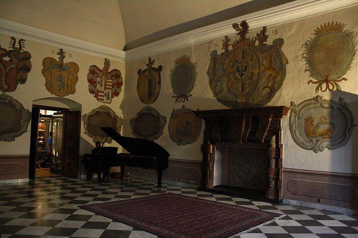 Harrach coat of arms on wall (top left), piano and fireplace in Kamenný sál (Stone hall) in Třebíč Castle.