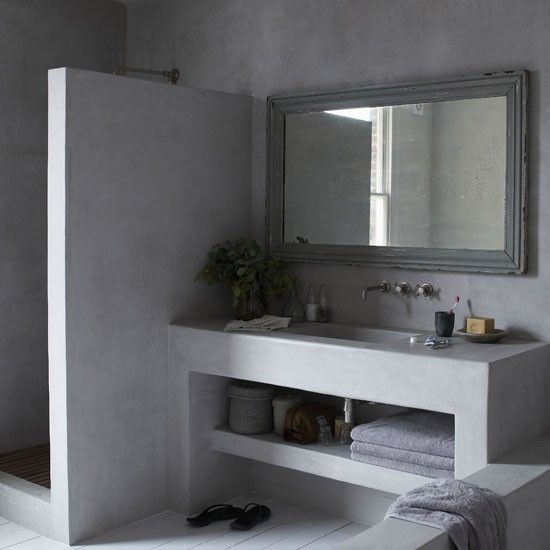 Concrete creates a seamless finish in this bathroom - from the shower and sink unit to the floor. A built-in shelf offers extra storage for that minimalist look.