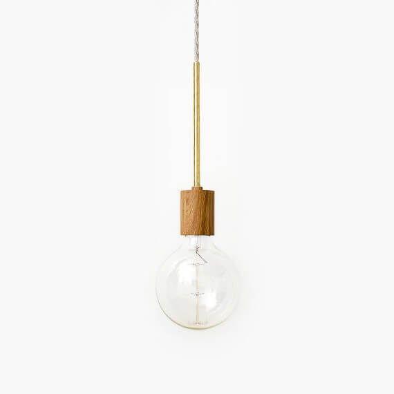 Een minimalistische pendel lamp in donker eikenhout en messing. Een eenvoudig ontwerp dat zorgt voor de perfecte sfeerverlichting. Wordt zonder
