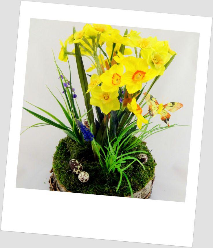 www.abgHomeArt.pl Ręcznie wykonany z dbałością o każdy szczegół wielkanocny stroik w podstawie wykonanej z kory brzozowej z kwitnącymi żonkilami, niebieskimi konwaliami i szafirkami na trawce otulone mchem. Udekorowany jajeczkami i motylkiem.     Efektowna i radosna wielkanocna dekoracja, która pięknie przyozdobi stół, komodę, czy też kominek, a także wprowadzi powiew wiosny. Idealny do każdego wnętrza.