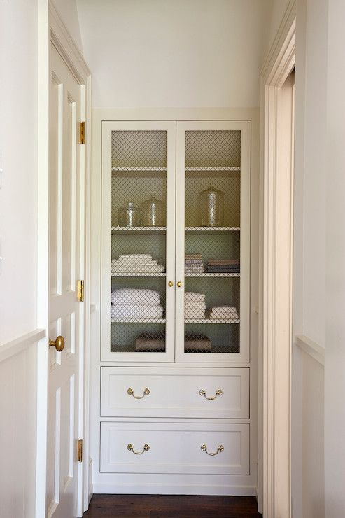 source: 3 North  Entry to bathroom features built-in linen cabinet with chicken wire doors accented with antique brass hardware. Hallway to bathroom with creamy white upper walls paired with chair rail and bottom walls painted Benjamin Moore Sailcloth.