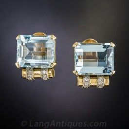 Chic and stylish, cool blue and rosy-yellow gold Retro Aquamarine earrings, circa 1940s. A matched pair of emerald-cut Aquas, weighing 18 carats total, and gleaming with a serene medium pastel blue color, are enhanced with a classic Retro scroll motif wrapped with a double row of tiny twinkling diamonds. 5/8 by just over 1/2 inch.