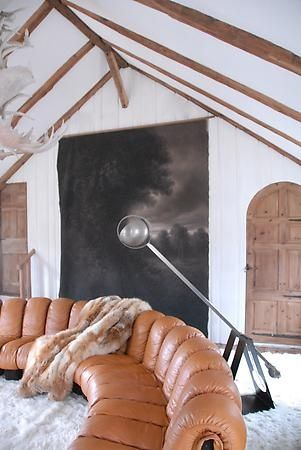 Vaulted ceiling, exposed beams, art work, leather sofa