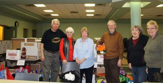 Volunteers with the Helping Hand Food Bank surrounded by Christmas Hampers, turkeys and hams, in the parish hall at Holy Martyrs of Japan Catholic Church in Bradford, Ont. on Tuesday December 22, 2015. Miriam King/Bradford Times/Postmedia Network