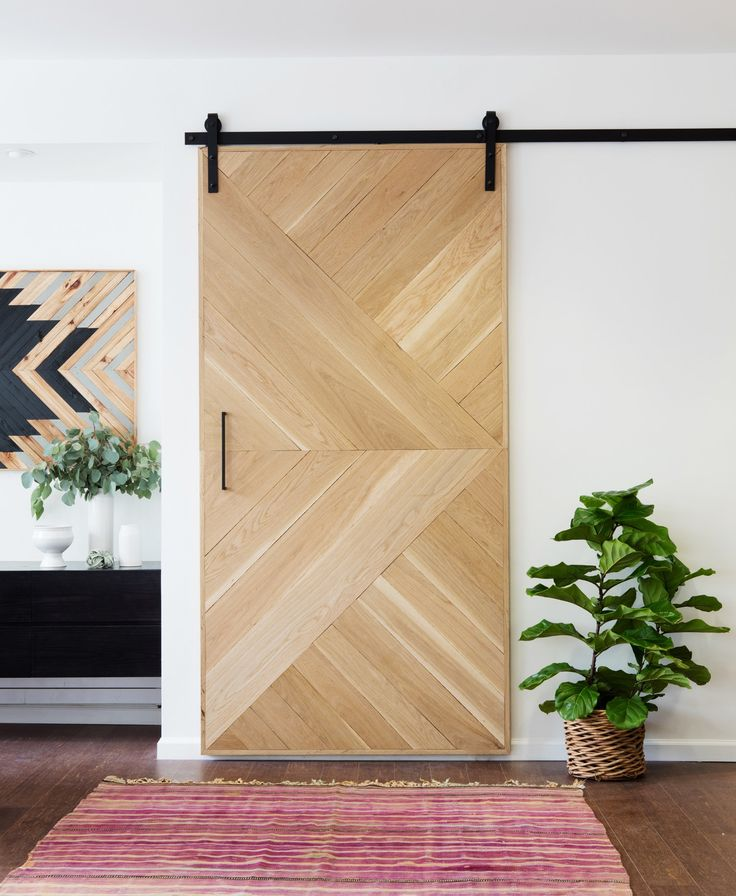 """Mix natural wood with clean, white walls,"" Nelson says. ""Here, the unfinished white oak paired with the matte black hardware creates a nice contrast, adding interest to the space."""
