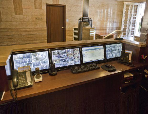 multiple monitor displays behind concierge desk security cameras email internet etc - Concierge Desk Design
