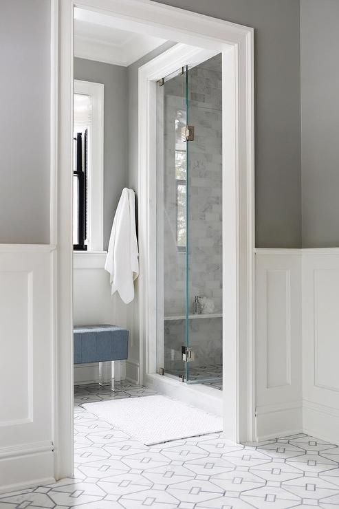 A white bath rug sits on white and gray marble geometric floor tiles in front of a seamless glass shower clad in linear marble wall tiles and fitted with a marble bench.