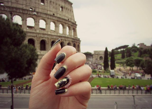 Black and gold reverse ruffian manicure at Colosseum in Rome