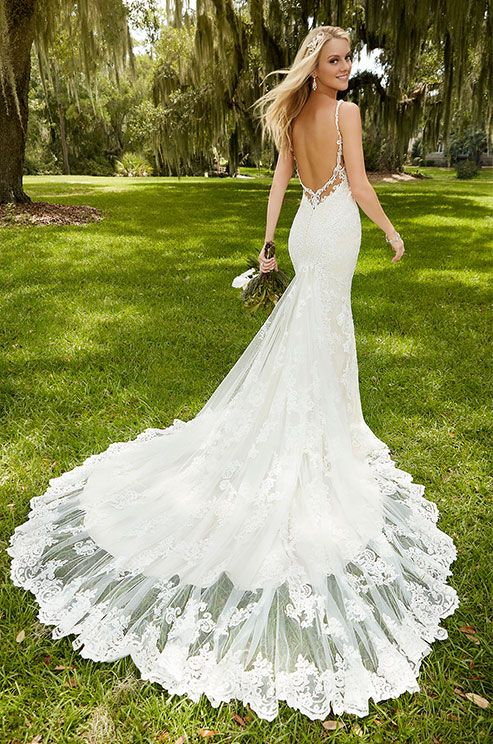 This breathtaking lace over satin fit-and-flare wedding dress from Martina Liana offers a sexy deep V neck and flirty peek-a-boo back.