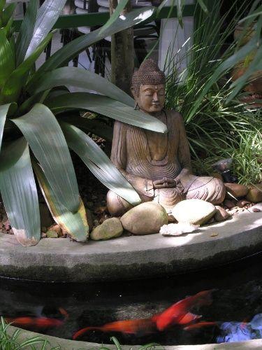 Uma imagem de Buda está posicionada junto ao espelho d'água com carpas. O paisagista João Jadão criou um jardim para o relaxamento em uma casa localizada em Alphaville, na Grande São Paulo
