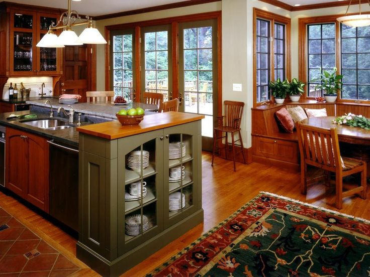 Situating a built-in dish armoire between the dishwasher and the eating area takes the effort out setting the table. This green cabinet, in a sea of rich browns, also gives the Arts-and-Crafts kitchen color and warmth. Learn more about Arts-and-Crafts Kitchens. Design by Thomas Conway