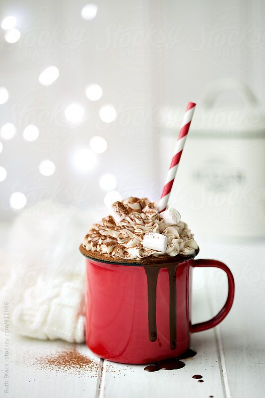 Hot cocoa with mini marshmallows, drizzled with chocolate syrup dripping over edge, maybe some sprinkles, on a blank surface where dripping chocolate is visible.