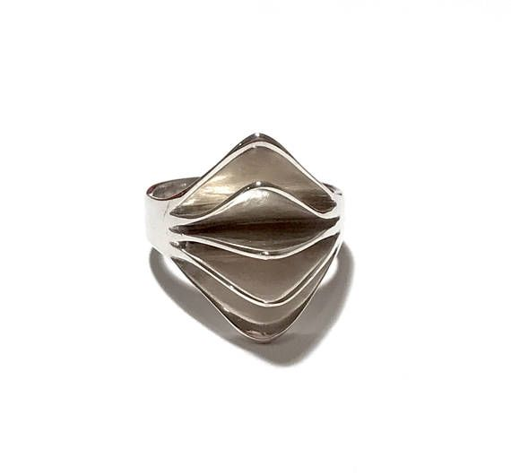 New listings daily follow us for updates.  An extremely stunning and unique #modernist Mid Century sterling silver statement ring, circa 1960s. The front of the ring comes to a rounded triangular point with four slic... #vintage #teamlove #etsyretwt #jewelry #jewellery #sculptural #curved #1960s