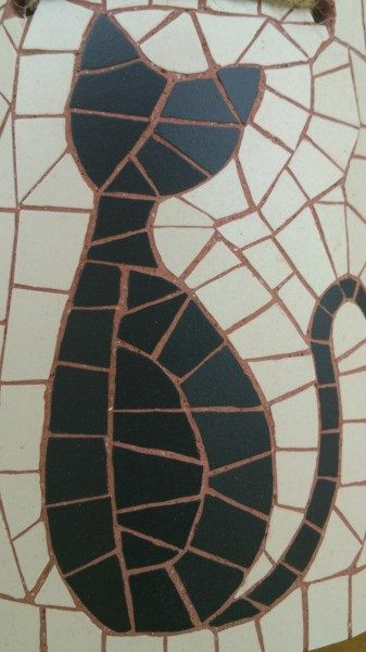 A cute black cat sitting in front of a white background.The mosaic is made of unglazed ceramic tiles,hand cut and glued on a cardboard roof tile.Its grouted in brick-red grout and the sides and back are painted in matching acrylic colour.The piece is finished with two coats of satin acrylic varnish for protection.  Dimensions:height;4.5 inch (11.5cm)   width:upper side:3.3 inch (8.5cm)   lower side: 3.9 inch (10cm)