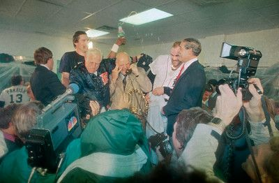 . Jim Campbell, President of the Detroit Tigers, center, takes a call from Pres. Ronald Reagan after the Tigers won the World Series, Sunday, Oct. 14, 1984, Detroit, Mich. Pitcher Jack Morris pours champagne over Campbell as manager Sparky Anderson, left, looks on. Others are Kirk Gibson and Bill Lajoie, general manager, right. (AP Photo/Richard Sheinwald)