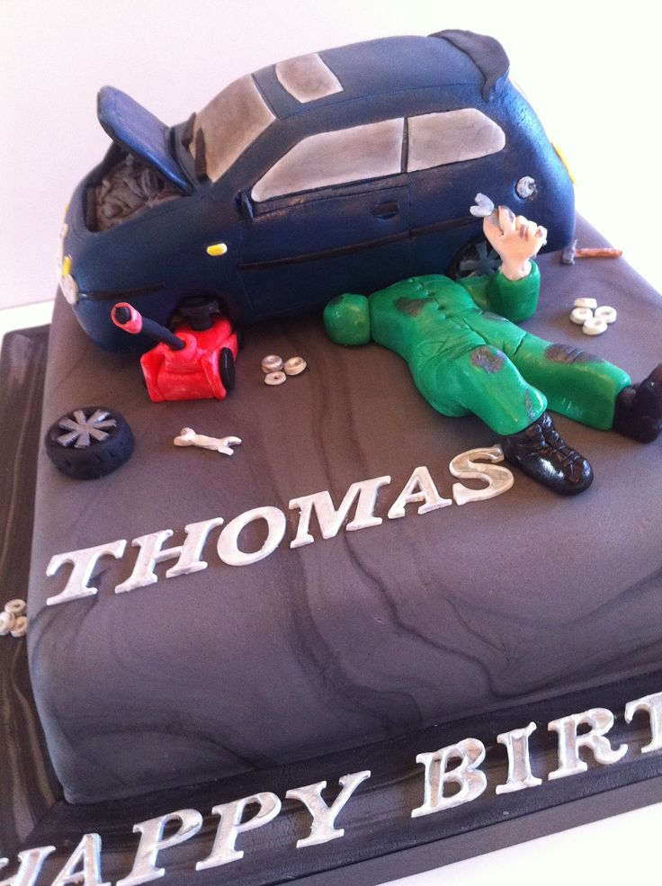A CAR MECHANIC CAKE complete with mechanic and VW Golf car with engine showing and car jack. July 2014