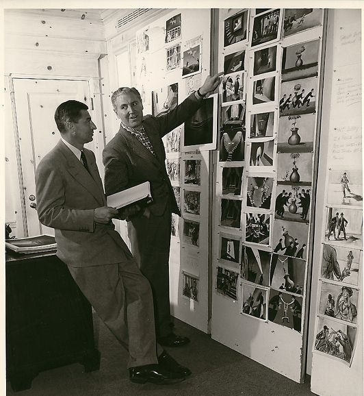 """This is a rare original photo of Ted Geisel--Dr. Seuss--looking over art direction and storyboards for his one totally Seussian feature film, ""The 5,000 Fingers of Dr. T""."""