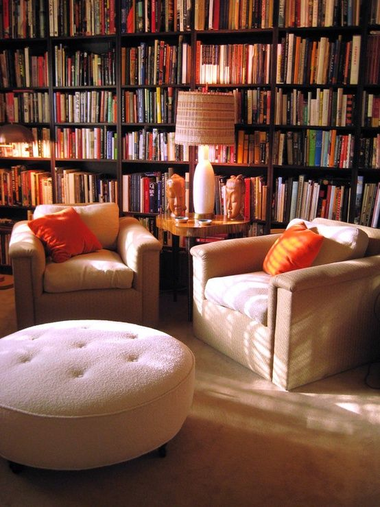 I love this library set-up!  Two cozy chairs, a table to set the coffee & hold a lamp, and a soft ottoman to plop my feet on.  And that wall of books isn't too shabby, either...