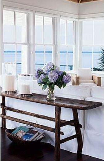 Rustic Cottage. Lovely Living Room. Beach House. Love the rustic console in contrast with the white upholstery. Gorgoues flowers look so beautiul with the blue ocean.. such a Serene room