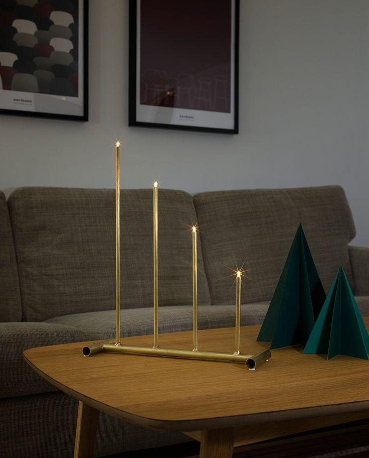 Adventsstake fra Konstsmide i råmessing med 4 lys. Staken har et røft og industrielt uttrykk hvor lysene hviler på en base av kappede metallrør.