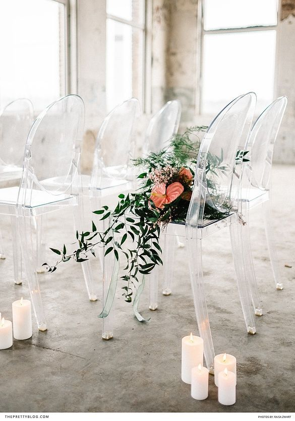 Wedding ceremony with ghost chairs, pink and green florals and white candles in a light and airy warehouse