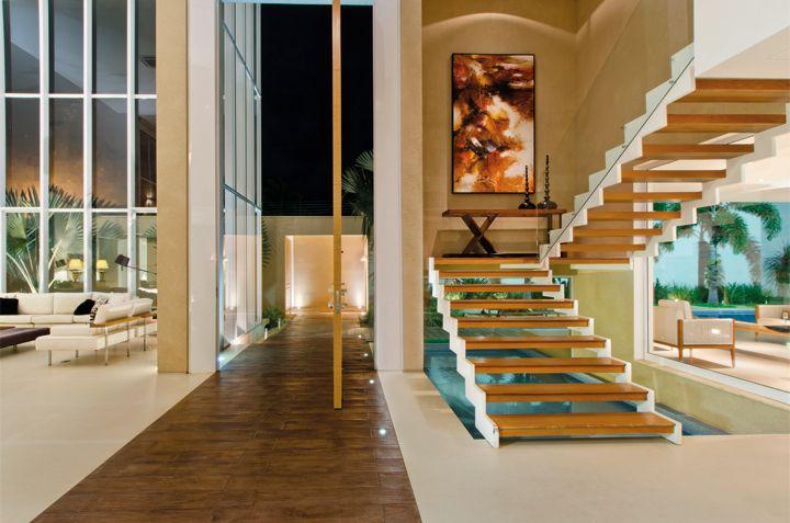 Confeccionada sob medida, a porta pivotante em alumínio madeira convida ao hall principal com piso setorizado pelo tapete de concreto da Segatto (Villaregio). Embaixo da escada com degraus vazados, o espelho d'água leva até a piscina
