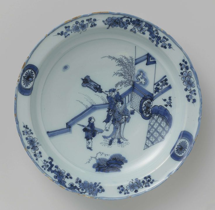 De Metaale Pot   Dish, De Metaale Pot, Lambertus Cleffius, c. 1680 - c. 1690   Schotel met licht geschulpte rand, van faience met een chinoiserie decoratie: beschilderd in blauw op witte, iets blauwige, glazuur met op het plat drie figuren bij een hek. Op de rand bloesemtakken en twee cartouches emt een rozet. Rand achterzijde met vakken waarin strepen en cirkels.