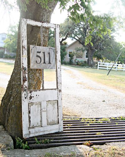 An old door posing as a house number frame... very cool! By Pennington Point via HomeTalk