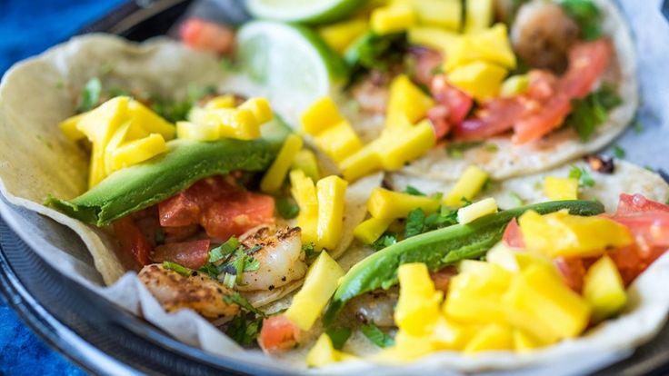 Tacos con gamberi, avocado, mango, pomodori e lime. Cibo e ricetta messicane