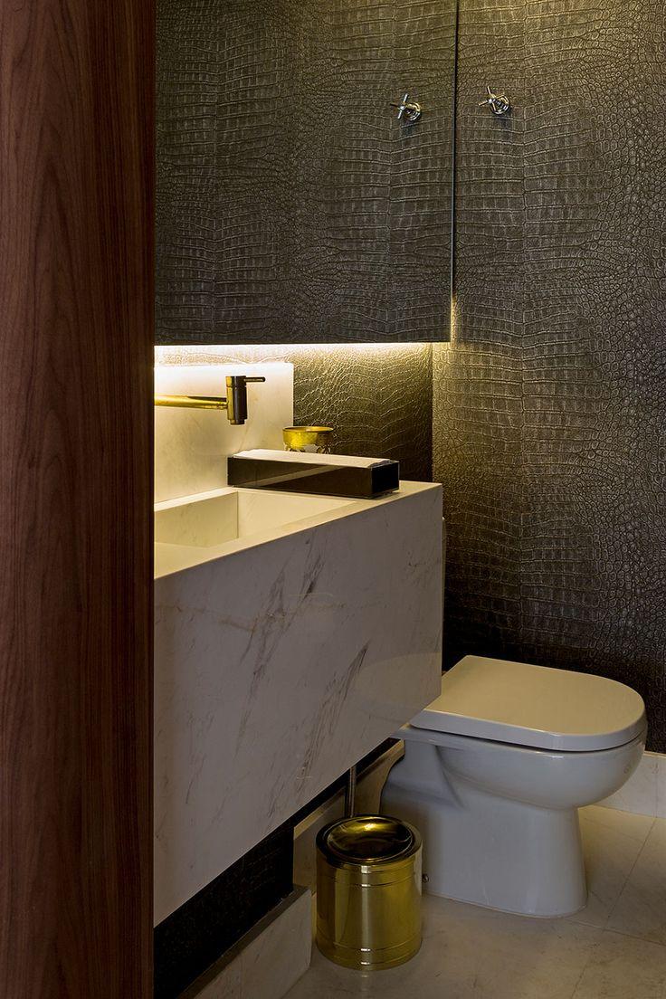 Banheiro com pia de mármore e detalhes em metal dourado.