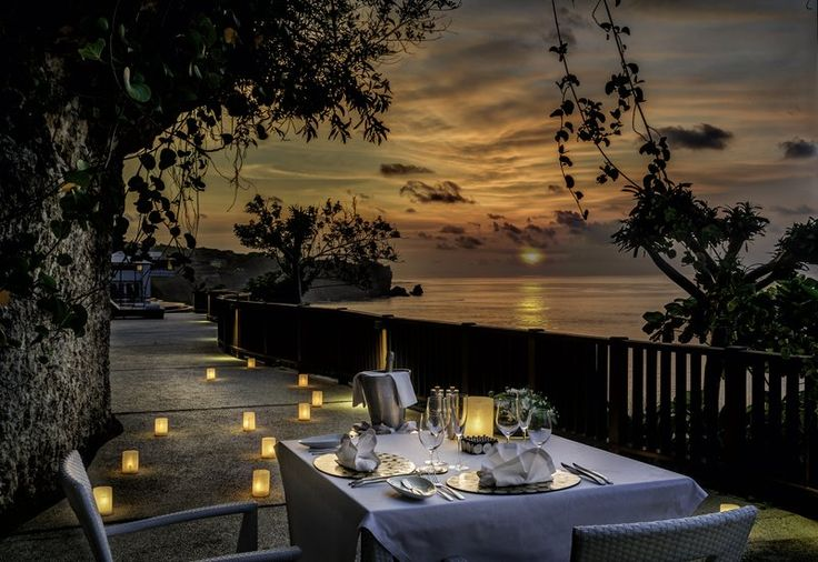 Dining By Design At The Cave. Romantic couples dinner by beach and sunset at Anantara Uluwatu Resort & Spa, Bali, Indonesia