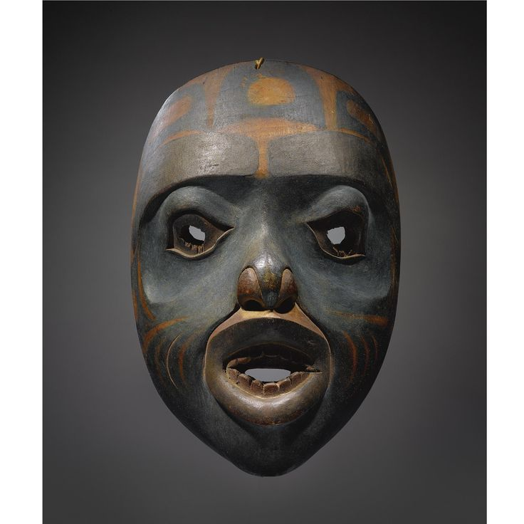 A TLINGIT POLYCHROMED WOOD MASK    composed of carved wood and pigments, probably depicting a devilfish or land otter man.   Height 9 1/2 in.
