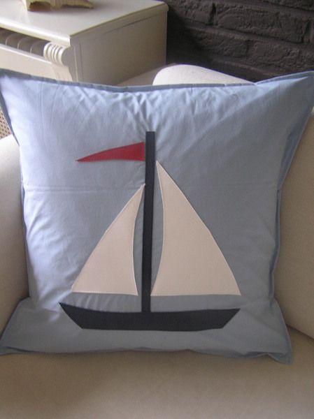 Lichtblauw kussen met applicatie van zeilboot in kunstleer. Leuk voor de kinderkamer.  De maat van het kussen is 50x50.  Het kussen is rondom d...