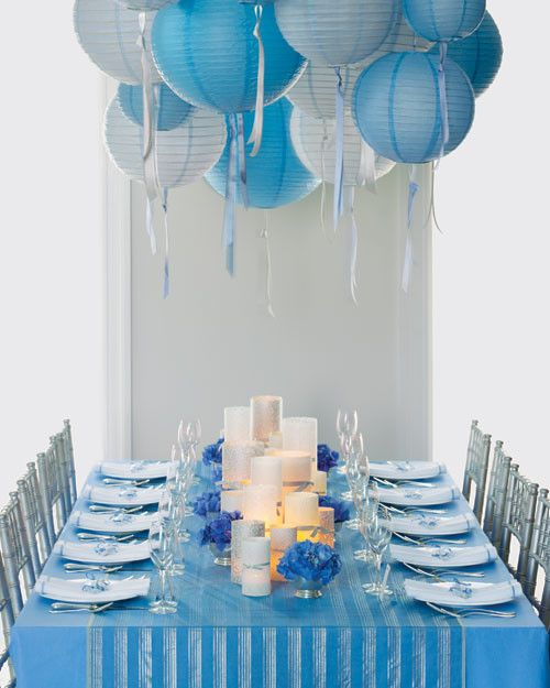 In this table setting, inexpensive beribboned lanterns in shades of blue make a big impact. A plain tablecloth is dressed up with a striped runner -- we just cut fabric to size and hemmed the ends. The simple centerpiece consists of glass candleholders wrapped in patterned paper and metallic ribbons, plus blue hydrangeas in silver footed bowls. Silver chairs and napkins with blue borders round out the motif.