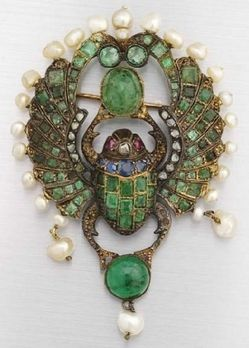 antiques price guide, antiques priceguide, jewelry, , An Egyptian Revival gem set scarab brooch, circa 1900. Emeralds, sapphires, pearls, rubies and rose-cut diamonds in yellow gold, partially silver-topped. Note: The winged scarab was a sacred Egyptian symbol of rebirth.